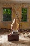 Junge Frau, die auf Weinlesekoffer sitzt Stockfoto