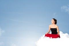 Junge Frau, die auf Wolke mit Kopienraum sitzt Lizenzfreies Stockfoto