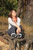 Junge Frau, die auf Wurzel sitzt stockfotos