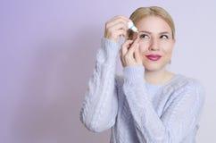 Junge Frau, die Augentropfen anwendet Stockfotos