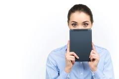 Junge Frau, die aus digitaler Tablette heraus schaut Stockfoto