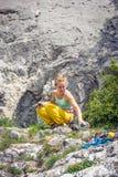 Junge Frau, die Ausrüstung für Klettern vorbereitet Lizenzfreie Stockfotos