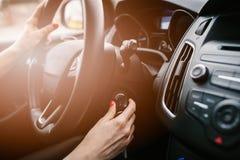 Junge Frau, die Automotor mit Schlüssel anläßt stockbild