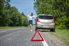 Junge Frau, die Autounterstützung nach Zusammenbruch auf dem ro fordert stockbilder