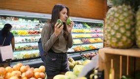 Junge Frau, die Avocados im Gemischtwarenladen wählt Null überschüssiges Mädchen des strengen Vegetariers kaufende Früchte und Ve stock footage