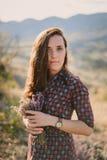 Junge Frau, die Bündel Wildflowers hält Lizenzfreie Stockfotos