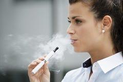 Junge Frau, die Bürogebäude der elektronischen Zigarette im Freien raucht Stockbilder