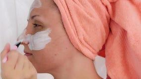 Junge Frau, die Bürste verwendet, um kosmetische Maske auf Gesicht anzuwenden Mädchen, eine Gesichtsmaske auf ihrer Backe anwende stock video footage