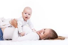Junge Frau, die Babysohn beim an zurück liegen hält Stockfotografie