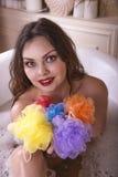 Junge Frau, die Bad mit hellen farbigen Schwämmen nimmt Stockfotos