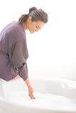 Junge Frau, die Badewanne vorbereitet Lizenzfreie Stockfotos