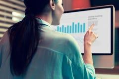 Junge Frau, die Balkendiagramme auf Computer studiert stockfoto