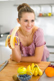 Junge Frau, die Banane in der Küche isst Lizenzfreie Stockfotografie