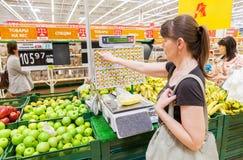 Junge Frau, die Bananen auf elektronischen Skalen im Erzeugnis dep wiegt Lizenzfreie Stockbilder