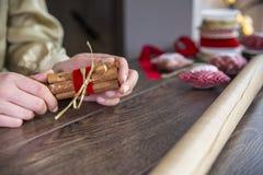 Junge Frau, die Band auf Geschenkbox auf hölzernem Hintergrund bindet stockfotografie