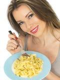 Junge Frau, die Bandnudeln-Teigwaren isst stockbilder
