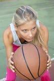 Junge Frau, die Basketball spielt stockbild
