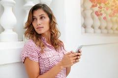Junge Frau, die bei der Anwendung des intelligenten Telefons weg schaut Stockfotografie
