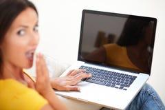 Junge Frau, die bei der Anwendung des Laptops überrascht schaut Stockfotografie