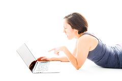 Junge Frau, die bei der Anwendung des Laptops entsetzt schaut Lizenzfreie Stockfotos