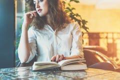Junge Frau, die bei Tisch im Café mit einem Papierbuch sitzt Mädchenwartefreunde im Restaurant- und Lesebuch Stockfoto