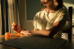 Junge Frau, die bei Tisch mit einer Orange sitzt Stockfoto