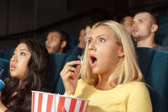 Junge Frau, die beim Aufpassen eines Films erschrocken schaut Stockbilder