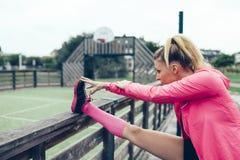 Junge Frau, die Beine ausdehnt, vor draußen ausbilden Lizenzfreie Stockfotos