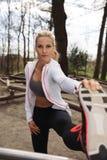 Junge Frau, die Beine vor einem Lauf ausdehnt Stockbild
