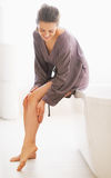 Junge Frau, die Beinhautweichheit im Badezimmer überprüft Stockfotos