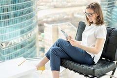 Junge Frau, die Berührungsfläche beim Sitzen im Büro verwendet Stockfotografie