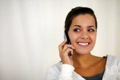 Junge Frau, die über das Mobiltelefon schaut recht spricht Lizenzfreie Stockfotografie