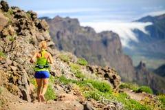Junge Frau, die in Berge läuft oder wandert Stockbild