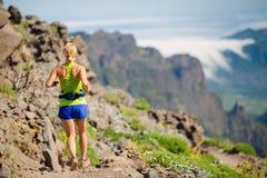 Junge Frau, die in Berge am Sommertag läuft Stockbilder