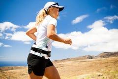 Junge Frau, die in Berge am sonnigen Sommertag läuft Stockfoto