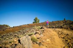 Junge Frau, die in Berge am sonnigen Sommertag läuft Lizenzfreie Stockfotos
