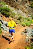 Junge Frau, die in Berge am sonnigen Sommertag läuft Stockbild