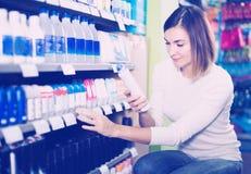 Junge Frau, die bestes desodorierendes Mittel wählt Lizenzfreie Stockbilder