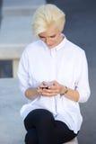 Junge Frau, die bewegliche Textnachricht liest Stockfotografie