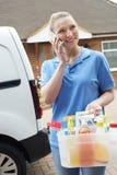 Junge Frau, die beweglichen Reinigungsbetrieb mit Van Using Mobi laufen lässt Stockbild