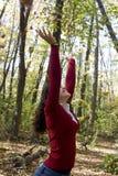 Junge Frau, die Blätter wirft Stockfotografie