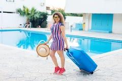 Junge Frau, die blaues Gepäck trägt und zum Erholungsort ankommt Sie geht nahe bei dem Swimmingpool Anfang von Lizenzfreies Stockfoto