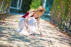 Junge Frau, die Blumenblätter aufhebt Lizenzfreie Stockfotografie