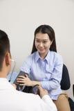 Junge Frau, die Blutdruck mit männlichem Doktor überprüft Lizenzfreies Stockfoto