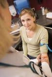 Junge Frau, die Blutprobe durchführen lässt Stockbild