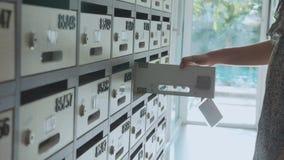 Junge Frau, die Briefkasten an der Eigentumswohnung, Innen überprüft stock video