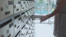 Junge Frau, die Briefkasten an der Eigentumswohnung, Innen überprüft stock footage