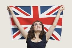 Junge Frau, die britische Flagge mit Stolz über grauem Hintergrund hält lizenzfreies stockbild