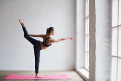 Junge Frau, die Übung auf Yogamatte ausdehnend tut Stockfotos