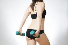 Junge Frau, die Übungen mit Dummköpfen tut Stockfotos
